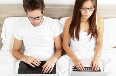 Couple on laptop computer in bed